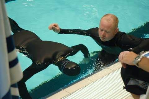 Sikkerheds makker ved statisk dyk med dommer og sikkerhed på kanten